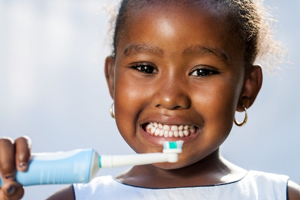 Little girl holding toothbrush and smiling